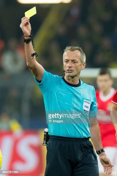 Referee Martin Atkinson Shows the yellow card during the UEFA Champions League Round of 16 Second Leg match between Borussia Dortmund and SL Benfica...