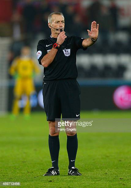 Referee Martin Atkinson signals during the Barclays Premier League match between Swansea City and Crystal Palace at Liberty Stadium on November 29...