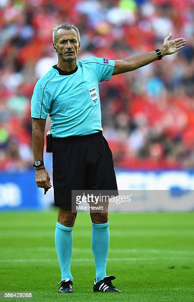 Referee Martin Atkinson signals during the International Champions Cup match between Liverpool and Barcelona at Wembley Stadium on August 6 2016 in...