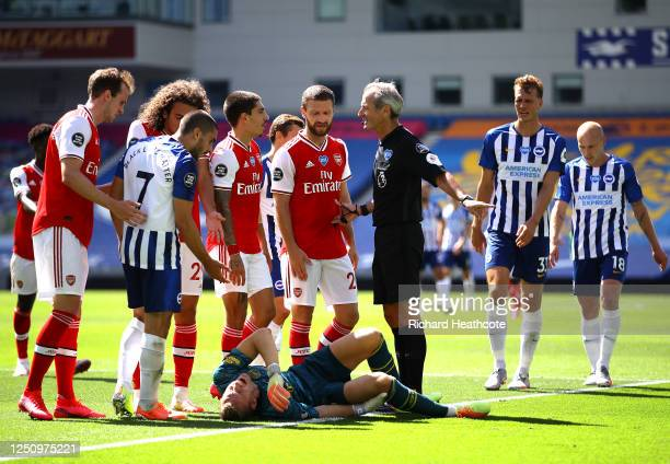 Referee Martin Atkinson speaks to Hector Bellerin and Shkodran Mustafi of Arsenal as Bernd Leno of Arsenal goes down injured as Neal Maupay of...