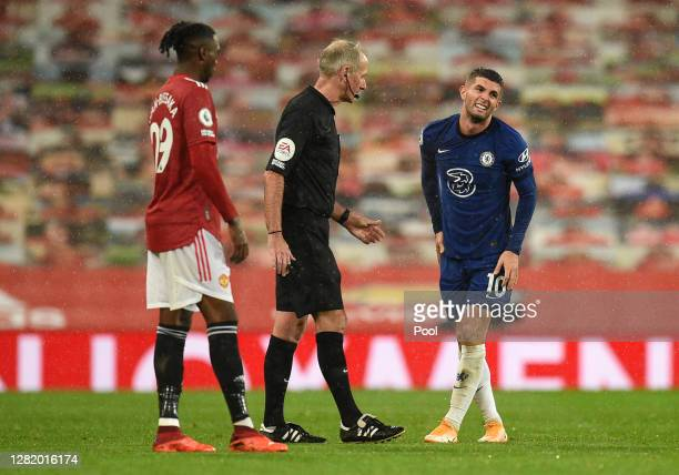 Referee Martin Atkinson speaks with Christian Pulisic of Chelsea who reacts after going down injured during the Premier League match between...