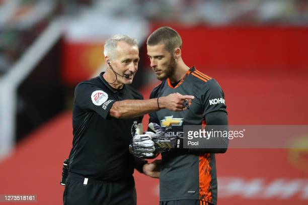 Referee Martin Atkinson speaks with David De Gea of Manchester United after David De Gea of Manchester United concedes a penalty from Crystal Palace...