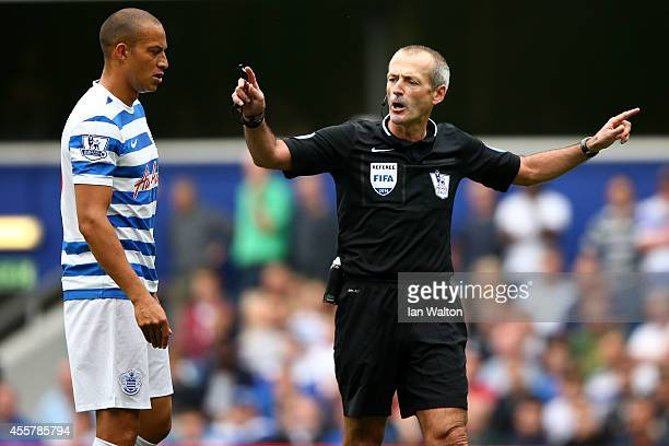 Referee Martin Atkinson talks to Bobby Zamora of QPR during the Barclays Premier League match between Queens Park Rangers and Stoke City at Loftus...