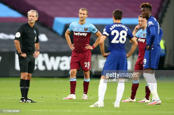Referee Martin Atkinson waits for a VAR decision of offside for a disallowed goal by West Ham United's Czech midfielder Tomas Soucek during the...