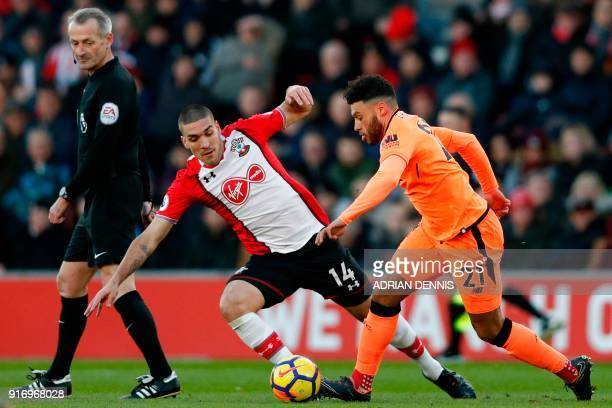 Referee Martin Atkinson watches on as Southampton's Spanish midfielder Oriol Romeu challenges Liverpool's English midfielder Alex OxladeChamberlain...