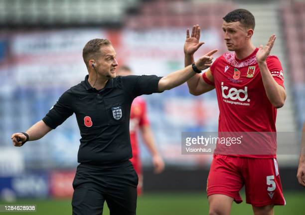 Referee Martin Coy waves away Scott Leather of Chorley FC during the FA Cup First Round match between Wigan Athletic and Chorley on November 8, 2020...