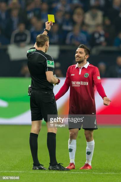 Referee Martin Petersen shows a yellow card to Julian Korb of Hannover during the Bundesliga match between FC Schalke 04 and Hannover 96 at...