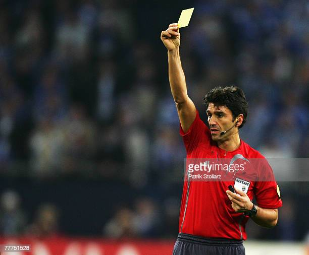 Referee Massimo Busacca shows a yellow card during the Group B match between Schalke and Chelsea at the Veltins Arena on November 6 2007 in...