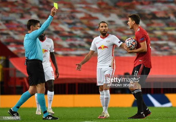Referee Matej Jug shows a yellow card to Manchester United's Serbian midfielder Nemanja Matic for a foul during the UEFA Champions league group H...