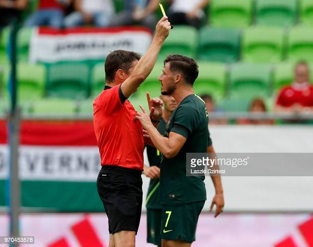 Referee Matej Vidali shows a yellow card for Mathew Leckie of Australia during the International Friendly match between Hungary and Australia at...