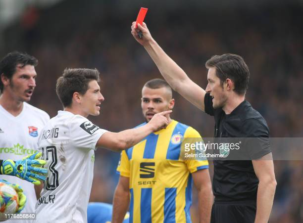 Referee Matthias Joellenbeck shows the red card to JimPatrick Mueller of SpVgg Unterhaching during the 3 Liga match between Eintracht Braunschweig...