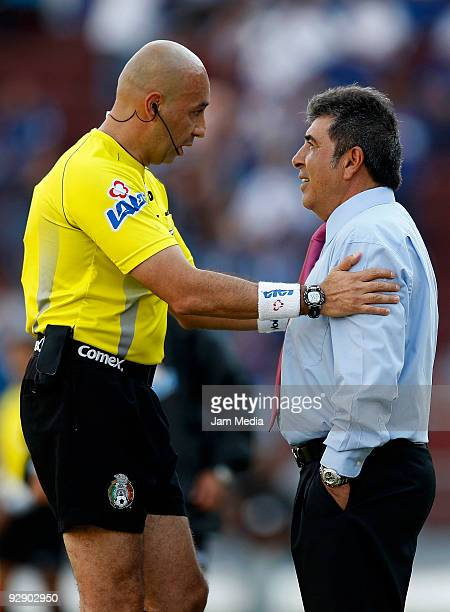 Referee Mauricio Morales speaks with Queretaro's Head Coach Carlos Reinoso during their match in the 2009 Opening tournament the closing stage of the...