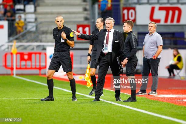 Referee Mehdi Mokhtari and League Delegate Alain Marseille speak together as the match is temporarily stopped in response to homophobic chants by...
