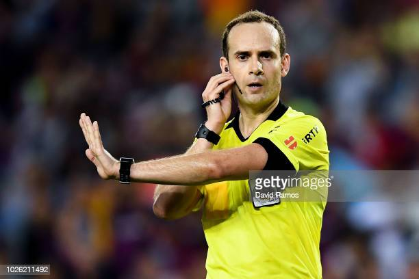 Referee Melero Lopez checks with the VAR during the La Liga match between FC Barcelona and SD Huesca at Camp Nou on September 2 2018 in Barcelona...