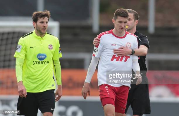 Referee Michael Bacher holds Markus Pazurek of Cologne beside Niklas Dams of Wiesbaden during the 3 Liga match between SC Fortuna Koeln and SV Wehen...