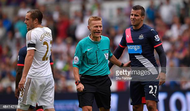 Referee Michael Jones shares a joke with Newcastle player Steven Tyalor during the Barclays Premier League match between Swansea City and Newcastle...