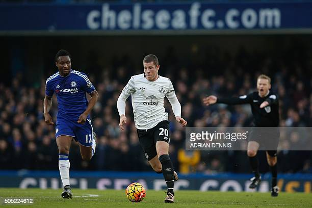 Referee Michael Jones waves play on as Everton's English midfielder Ross Barkley runs with the ball chased by Chelsea's Nigerian midfielder John Obi...