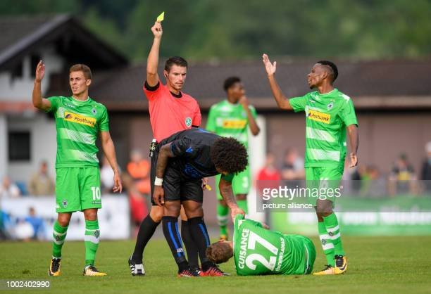 Referee Michael Kempter pulls a yellow card on Nice's Dante as Moenchengladbach's Michael Cuisance lies on the pitch, with Moenchengladbach's Thorgan...