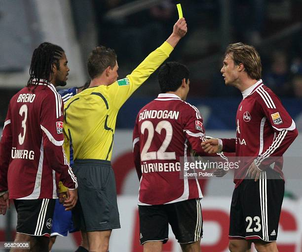 Referee Michael Kempter shows the yellow card to Andreas Ottl during the Bundesliga match between FC Schalke 04 and 1. FC Nuernberg at Veltins Arena...