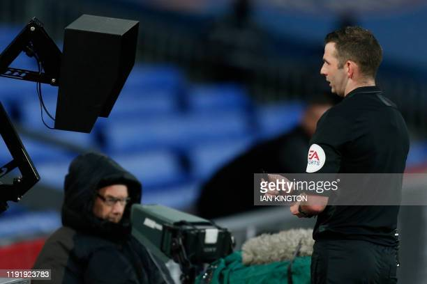 Referee Michael Oliver checks the VAR pitchside monitor during the English FA Cup third round football match between Crystal Palace and Derby County...