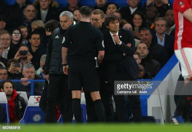 Referee Michael Oliver confers with fourth official Mike Jones as he speaks to Jose Mourinho Manager of Manchester United and Antonio Conte manager...