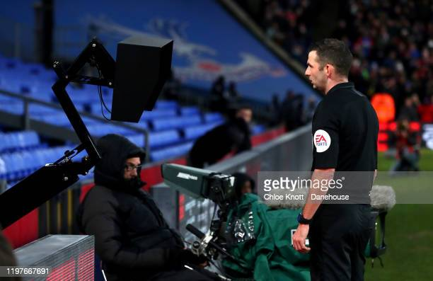 Referee Michael Oliver consults the VAR screen during the FA Cup Third Round match between Crystal Palace and Derby County at Selhurst Park on...