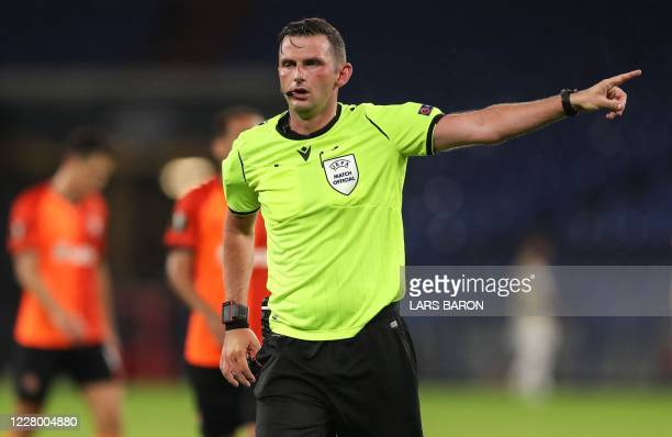 Referee Michael Oliver gestures during the UEFA Europa League quarter-final football match Shakhtar Donetsk v FC Basel at the Arena Aufschalke on...