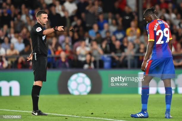 Referee Michael Oliver gestures to Crystal Palace's English midfielder Aaron WanBissaka after he sent him off during the English Premier League...