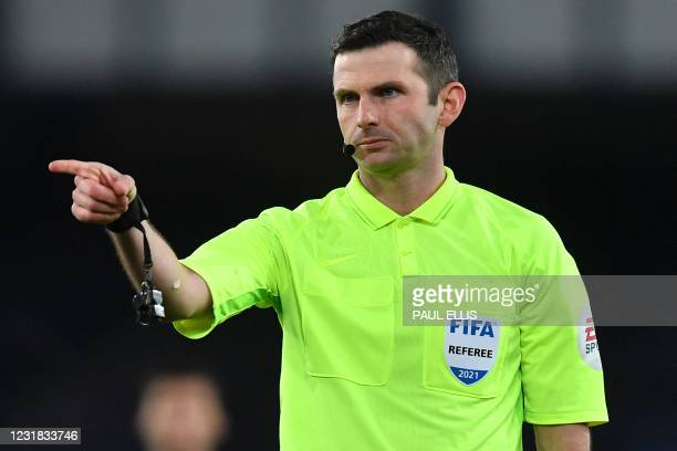 Referee Michael Oliver points during the English FA Cup quarter final football match between Everton and Manchester City at Goodison Park in...