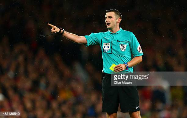 Referee Michael Oliver prepares to issue a yellow card during the Barclays Premier League match between Arsenal and Liverpool at the Emirates Stadium...