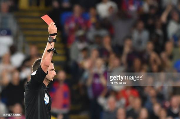 Referee Michael Oliver raises the red card to send off Crystal Palace's English midfielder Aaron WanBissaka during the English Premier League...