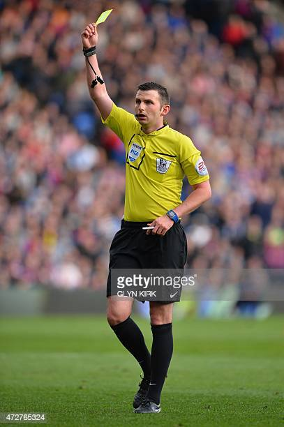 Referee Michael Oliver shows a yellow card during the English Premier League football match between Crystal Palace and Manchester United at Selhurst...