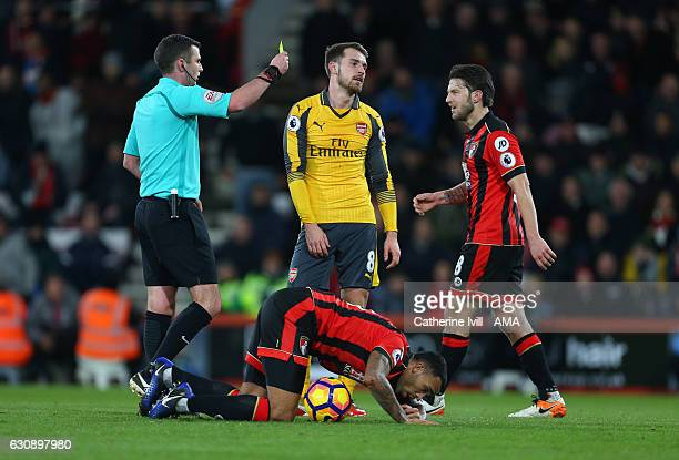 Referee Michael Oliver shows Aaron Ramsey of Arsenal a yellow card during the Premier League match between AFC Bournemouth and Arsenal at Vitality...