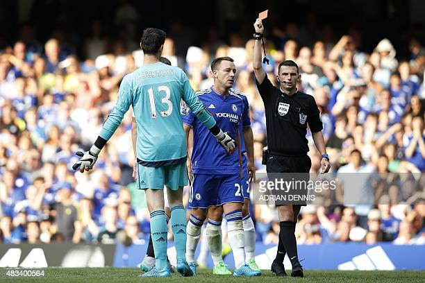 Referee Michael Oliver shows the red card to send off Chelsea's Belgian goalkeeper Thibaut Courtois after a foul on Swansea City's French striker...