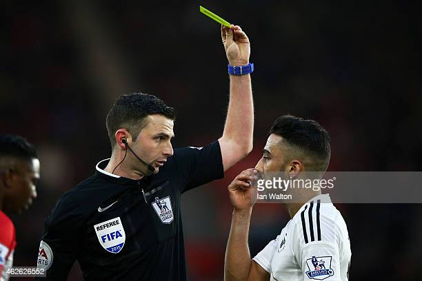 Referee Michael Oliver shows the yellow card to Neil Taylor of Swansea City during the Barclays Premier League match between Southampton and Swansea...