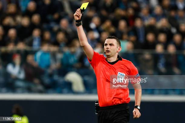 Referee Michael Oliver shows yellow card during the UEFA Europa League Round of 32 second leg match between FC Zenit Saint Petersburg and Fenerbahce...