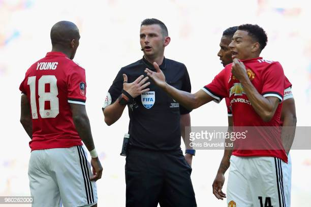 Referee Michael Oliver talks with Ashley Young and Jesse Lingard both of Manchester United during the Emirates FA Cup Final between Chelsea and...