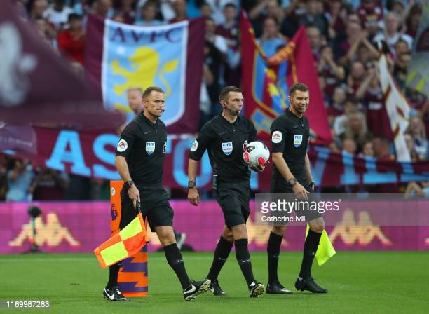 Referee Michael Oliver walks out with assistants Stuart Burt and Simon Bennett during the Premier League match between Aston Villa and Everton FC at...
