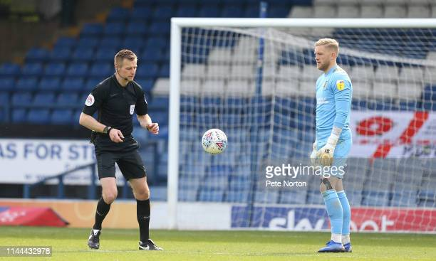 Referee Michael Salisbury restarts the game with a drop ball as David Cornell of Northampton Town looks on during the Sky Bet League Two match...