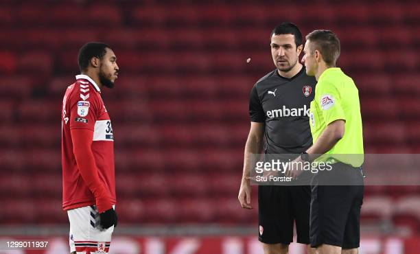 Referee Michael Salisbury tosses the coin as captains Britt Assombalonga and Richard Wood watch during the Sky Bet Championship match between...