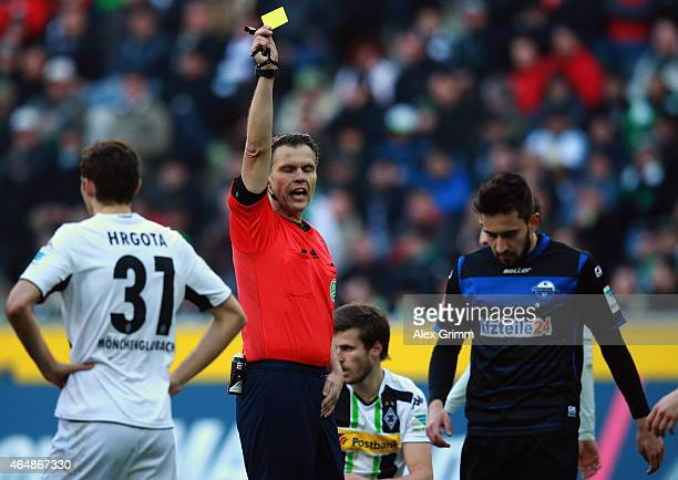 Referee Michael Weiner shows the yellow card to Lukas Rupp of Paderborn during the Bundesliga match between Borussia Moenchengladbach and SC...