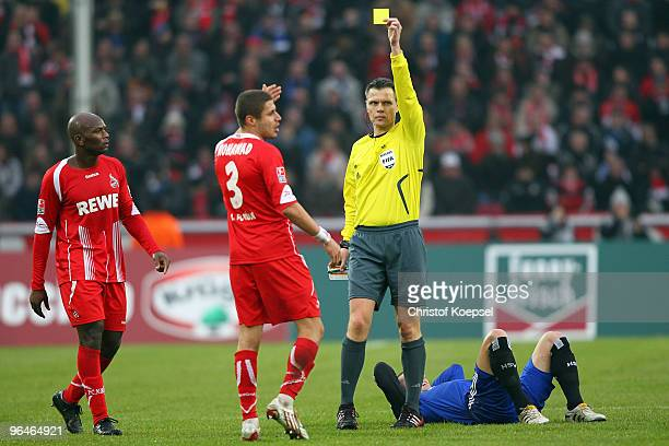 Referee Michael Weiner shows Youssef Mohamad of Köln the yellow card during the Bundesliga match between 1. FC Koeln and Hamburger SV at the...