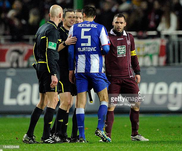 Referee Michael Weiner smiles with Andre Mijatovic of Berlin and Christian Tiffert after the Bundesliga match between 1FC Kaiserslautern and Hertha...