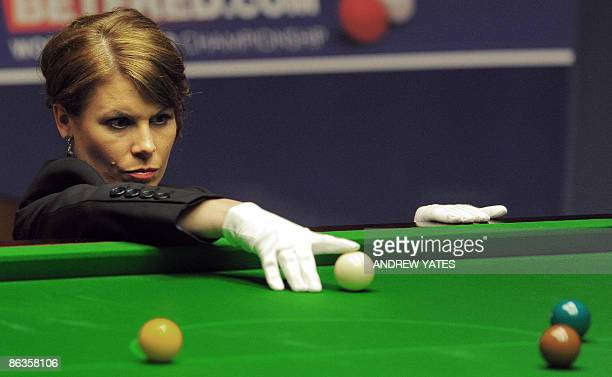 Referee Michaela Tabb places the cue ball during the World Championship Snooker final between Scotland's John Higgins and Britains Shaun Murphy at...