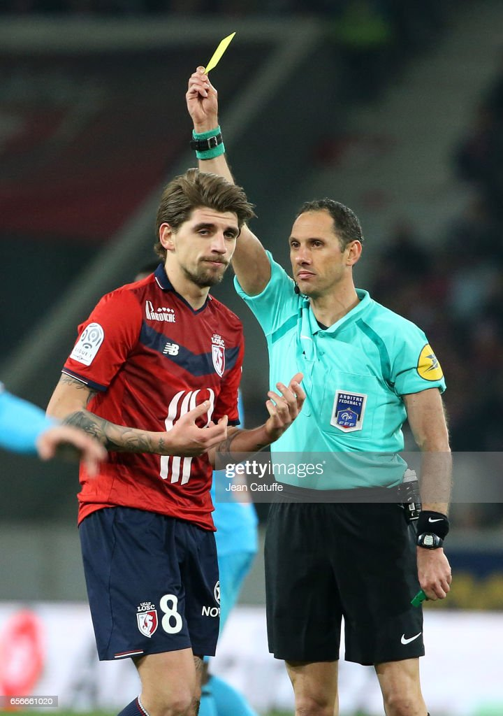 Referee Mikael Lesage gives a yellow card to Xeka of Lille during the French Ligue 1 match between Lille OSC (LOSC) and Olympique de Marseille (OM) at Stade Pierre-Mauroy on March 17, 2017 in Lille, France.