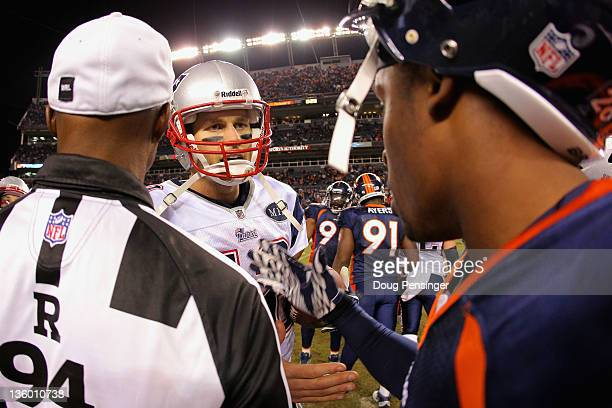 Referee Mike Carey looks on as quarterback Tom Brady of the New England Patriots and cornerback Champ Bailey of the Denver Broncos meet at midfield...