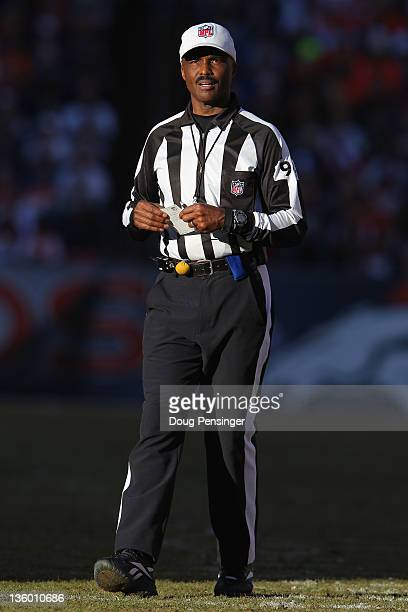 Referee Mike Carey looks on during a break in the action between the New England Patriots and the Denver Broncos at Sports Authority Field at Mile...