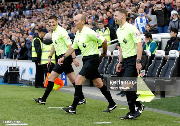 Referee Mike Dean and officials walk onto the pitch prior to the Premier League match between Brighton Hove Albion and Newcastle United at American...