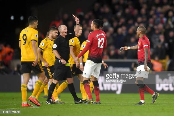 Referee Mike Dean awards Ashley Young of Manchester United a red card during the Premier League match between Wolverhampton Wanderers and Manchester...