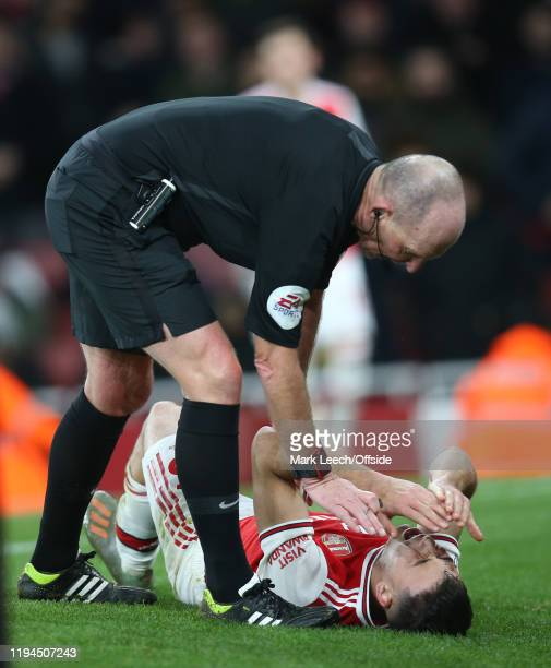 referee Mike Dean checks on an injury to Gabriel Martinelli of Arsenal during the Premier League match between Arsenal FC and Sheffield United at...